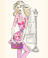Wall Mural - Young beautiful sexy woman in fashion sketch style. Street style girl wearing pink dress with city background vector
