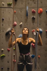 Confident female athlete holding ropes while standing against