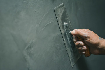 Hand of man working plastering on wall