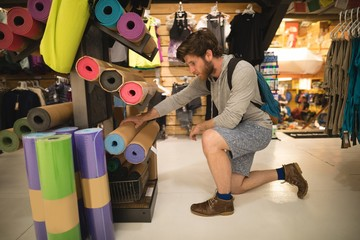 Man examining exercise mats in shop