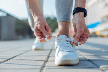 Close up of female hands tying shoelaces on sneakers