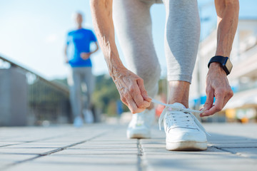 Close up of elderly woman tying shoelaces on sneakers