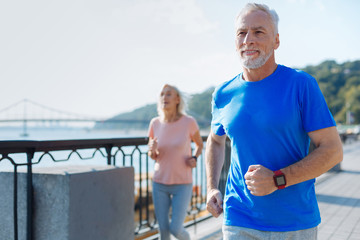 Fit senior man jogging together with his wife