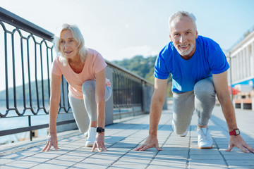 Upbeat elderly couple being about to start race