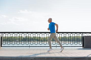 Side view of energetic senior man jogging on the bridge