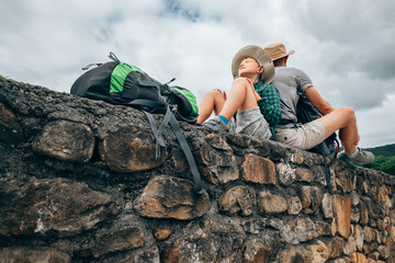 Father and son backpacker traveler rest together on old stone wall