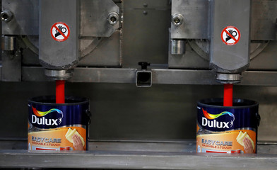 Dulux paint cans are filled on the production line inside AkzoNobel's new paint factory in Ashington, Britain