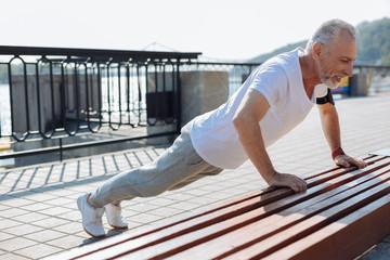Well-built senior man doing push-ups from bench