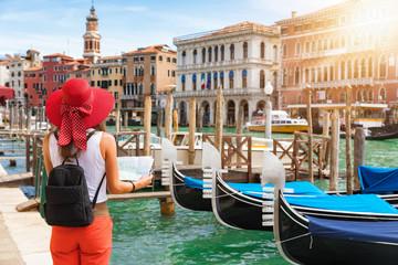 Touristin mit Sonnenhut steht mit einer Landkarte in der Hand am Canale Grande in Venedig, Italien