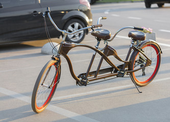 A tandem bicycle with scarlet wheel rims is parked in a parking lot in the evening sun.