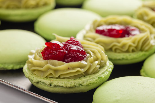 Green macaroons with pistachios ganache cream and raspberries confit filling