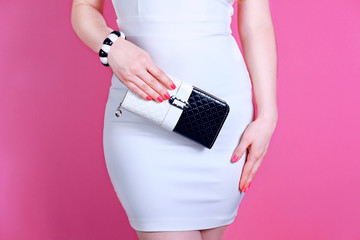 Wall Mural - Woman with black and white purse in hand . Stylish accessory