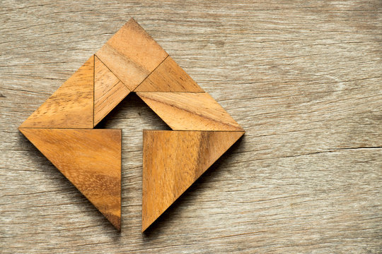 Tangram puzzle in square shape with the arrow symbol inside on wood background