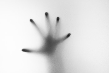 Shadow of hand the white frosted glass