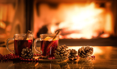 Mulled wine glasses on table in front of burning fireplace.