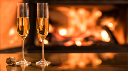 Champagne in two glasses on table in front of burning fireplace.