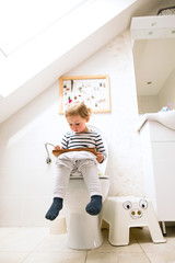 Little girl with tablet sitting on the toilet.