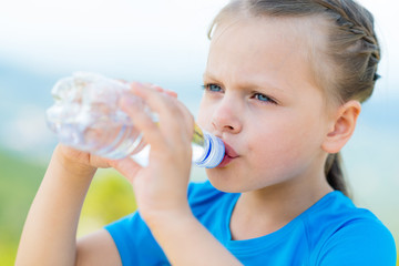 little girl drinking fresh water from bottle on light nature background