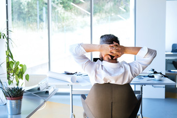 Wall Mural - Businessman at the desk in his office resting.