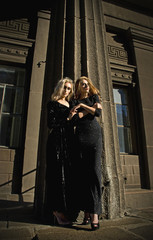 Two beautiful girls with blonde hair in long black fashion dresses in the front of the high biding