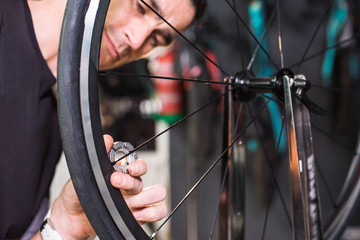 Closeup of male technician repairing a bike