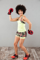 Full-length image of happy sports woman posing with boxing gloves