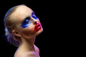 female portrait with creative multicolored makeup on black background
