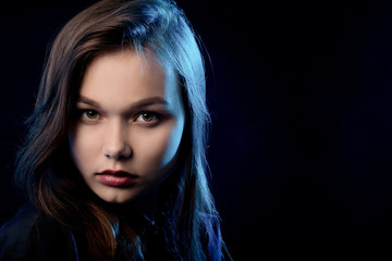 beautiful young sad woman in blouse at black background looking at camera