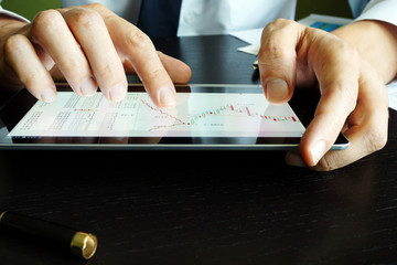 Trader holding tablet with stock market graph. Trading.