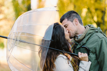 Lovely young couple kissing in autumn at the park. Romantic man and woman in love outdoor in fall season.