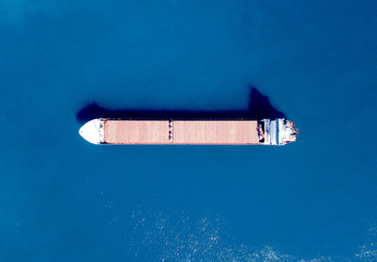 Large bulk carrier ship sailing in open ocean - top down aerial view
