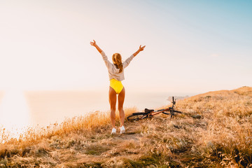 Happy beautiful woman in yellow clothes and in white sneakers with a mountain bike in nature.