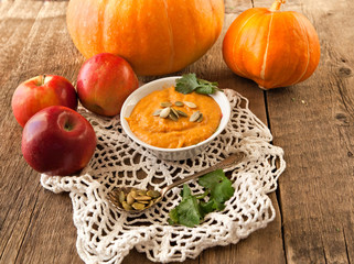 Halloween pumpkin, apple and pumpkin soup on old rustic wooden boards