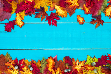 Blank teal blue wood sign with colorful autumn leaves border