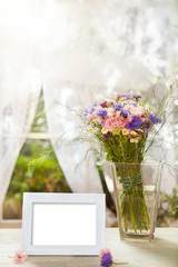 White frame and vase with flowers