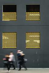 Blurred people in front of the building with yellow fences