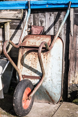 wheelbarrow against a shed