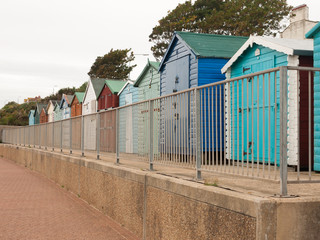a nice even row of beach huts with fence in front down in dovercourt harwich