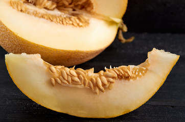 Fresh sweet yellow melon sliced on wooden black table. A piece of raw organic melon on wooden dark surface close up