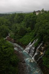 Beautiful Shirogane Falls dropping into a blue river, Biei, Hokkaido, Japan