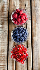Berries overhead mix raspberry blueberry currant in three glass jars on old rustic wooden table in studio
