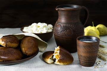 Milk, cottage cheese, pies in earthenware, pears