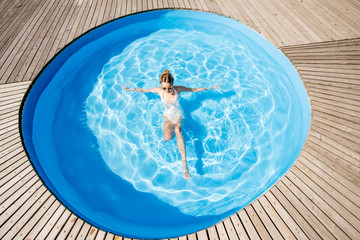 Top view on the round water pool with woman swimming outdoors