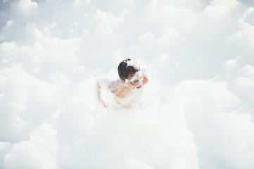 Cheerful kid playing in white foam