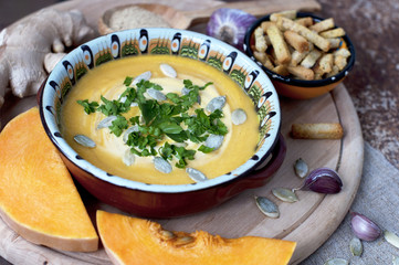 Pumpkin cream soup with crackers and ginger, parsley and  seeds