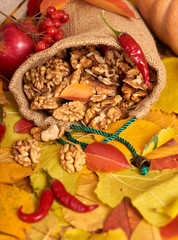 Nuts in a sack, fruits and vegetables on fallen leaves background, autumn season