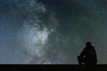 Milky Way. Night sky with stars and silhouette alone man looking at starry sky. Wall mural