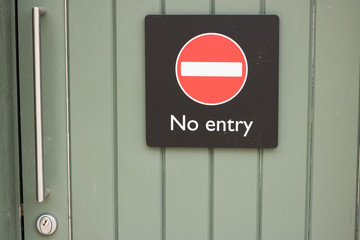 """Closed green door with an international obvious sign """"No entry"""". Concept: important signs and symbols."""