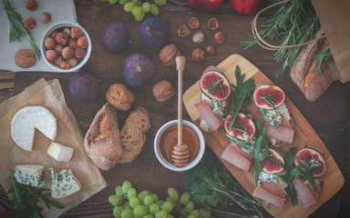 Sandwiches with ricotta, fresh figs, prosciutto, rosemary and blue cheese, walnuts and honey on rustic wooden board over black backdrop, top view. Delicious fruity breakfast. Toned