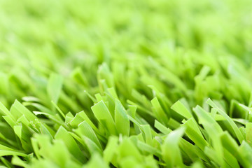 Green artificial grass texture with blurred background. Modern soft tender backdrop. Exterior interior material.